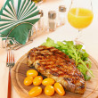 Ribeye steak on a wooden plate — Stock Photo