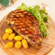 Ribeye steak on a wooden plate - Stock Photo