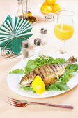 Fried fish Dorada on a laid table — Stock Photo