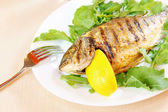 Fried fish Dorada with lemon and greenery — Stock Photo