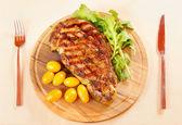 Ribeye steak on a wooden plate — Stock Photo