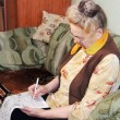 Stock Photo: Elderly womis reading newspaper