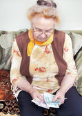 Elderly woman is counting the money — Stock Photo