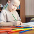 Little boy is learning to draw with pencils (focus on pencils) — Stock fotografie #14340053