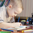 Little boy is drawing with colorful pencils in a book — Stock Photo