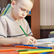 Stock Photo: Little boy is learning to draw with pencils (focus on the boy)