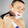 Man is shaving with axe — Stock Photo