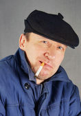 Marginal man in a cap with a cigarette — Stock Photo