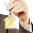 Keys with keychain in the form of a house in a male arm — Stock Photo