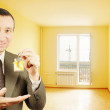 Man shows keys with keychain in the form of a little house into a new flat — Stock Photo