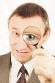 Angry man looks through a magnifying glass — Stock Photo