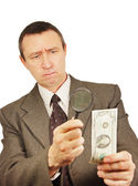 Serious man looks through a magnifying glass on the dollar — Stock Photo