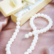 Pearl necklace on a beige silk fabric — Stock Photo #21660833