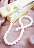 Pearl necklace on a beige silk fabric — Stock Photo