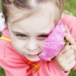 Stock Photo: Beautiful girl gently presses to cheek big pink flower