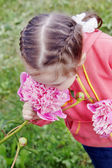 Little pretty girl inhales the scent of a big pink flower — Stock Photo