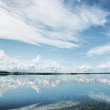 Beautiful summer landscape with reflection of cumulus clouds on water — Stock Photo