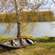 Autumn riverbank with old wooden boat — Stock Photo