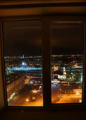 View of night city through a window — Stock Photo