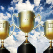 Three trophy cups against cloudy sky — Stock Photo #35178741