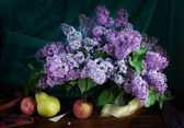Still life with bunch of blossoming purple lilac and fruits — Stock Photo