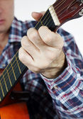 Man plays a chord on guitar — Stock Photo