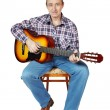 Man plays a guitar sitting on an chair — Stock Photo