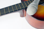 Microphone lying on a guitar — Stock Photo