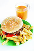 Hamburger with French fries in the plate and a glass of juice — Stock Photo