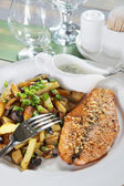 Piece of fried fish with potatoes on a table in cafe — Stock Photo