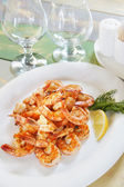 Lots of shrimps in a plate on the served table — Photo