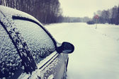Car on a snowy road (focus on the mirror) — Stock Photo