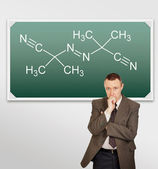 Scientist chemist stands by a blackboard with the formula — Stock Photo