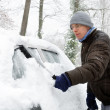 Stock Photo: Mremoves snow from his car