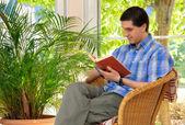 享受着一本书在家里的人 — 图库照片
