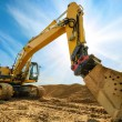Big excavator in front of the blue sky — Stock Photo