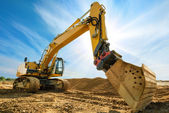 Excavador grande delante del cielo azul — Foto de Stock