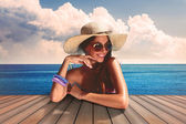 Girl with sunglasse and straw hat at the sea — Stock Photo