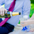 Groom pours champagne glasses in hand bride — Stock Photo