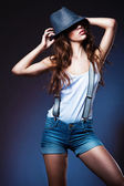 Sexy pretty woman in shorts with suspenders in hat — Stock Photo