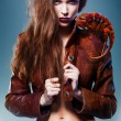 Pretty erotic devil woman in leather jacket with chameleon — Stock Photo #13132048