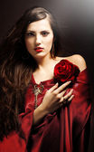 Attractive woman in red drapery with red rose — Stock Photo