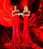 Two women in red dress with present in hands — Stock Photo