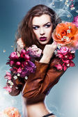 Pretty attractive erotic woman in brown jacket with big flowers — Stock Photo