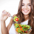 Happy healthy woman with salad on fork - Photo