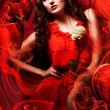 Beautiful hot woman in love in red dress around fabric and heart — Stock Photo #14058724