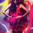Brunette womin sunglasses and red dress around fabric — Stock Photo #14058769