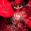 Goddess of love in red dress with long hair and hearts — Stock Photo