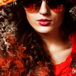 Hot brunette woman in sunglasses with fire — ストック写真