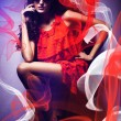 Sexy womin sunglasses and red dress around red and white fabr — Stock Photo #14058884